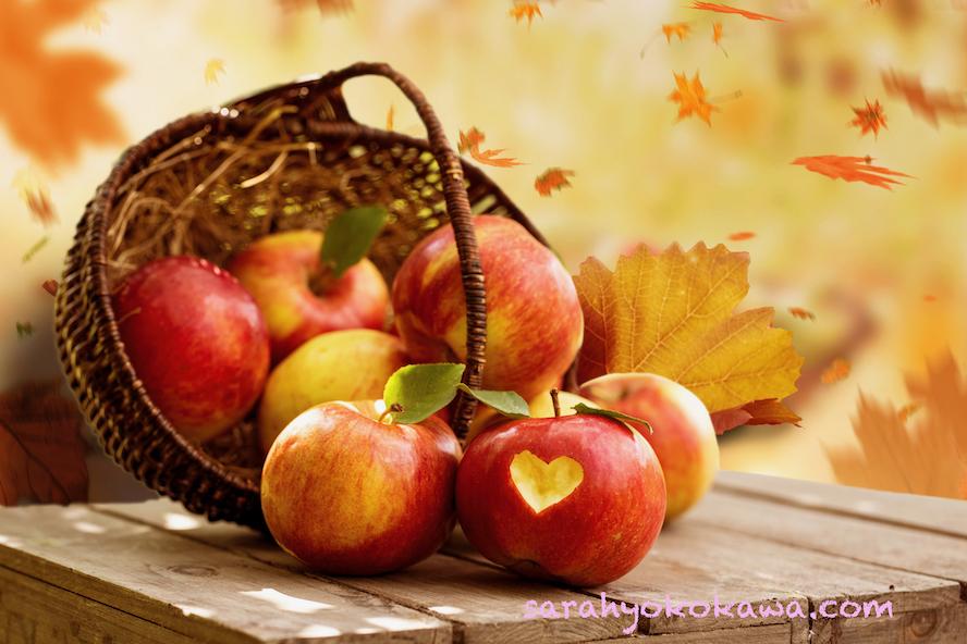 Ein Holzkorb mit frischen,roten, leckeren Äpfeln auf einem rustikalen Holztisch. Vor Herbstlandschaft im Hintergrund mit Herbstblättern. Licht und Sonne.